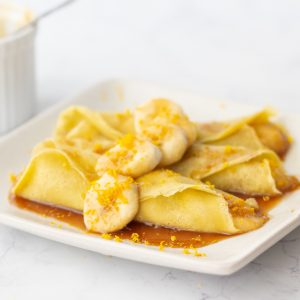 square white plate with 3 gluten-free banana crepes with orange glaze with white syrup bowl in background
