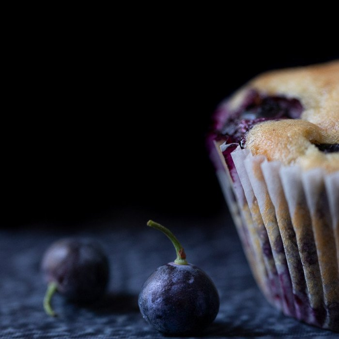 close up of 2 blueberries with stems and half visible gluten-free blueberry muffin on right. Black background.