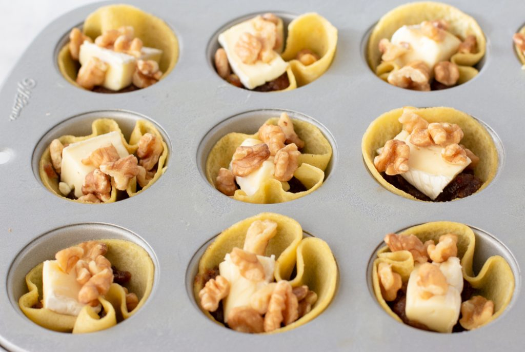 mini muffin tin with gluten-free tartlettes with date, brie chunk and chopped walnuts