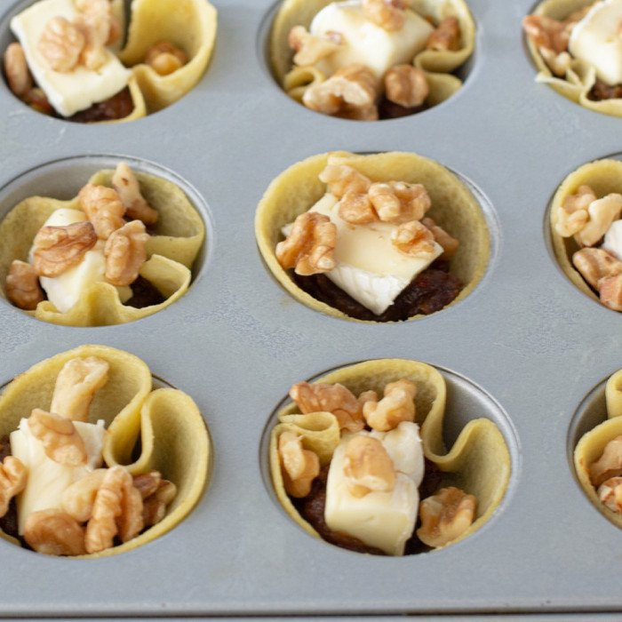overhead view of mini muffin tin with brie and date tartlettes with walnuts