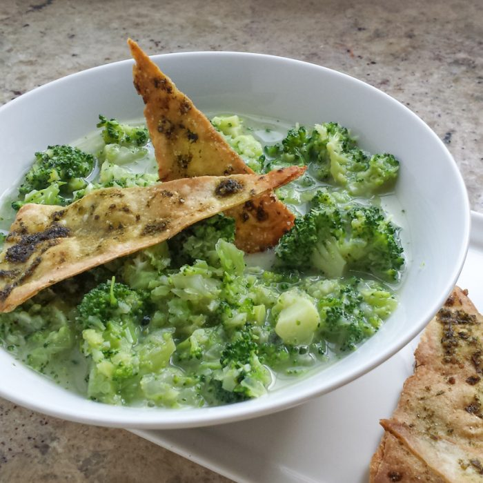 chunky broccoli soup in round white board with triangular basil flavored chips