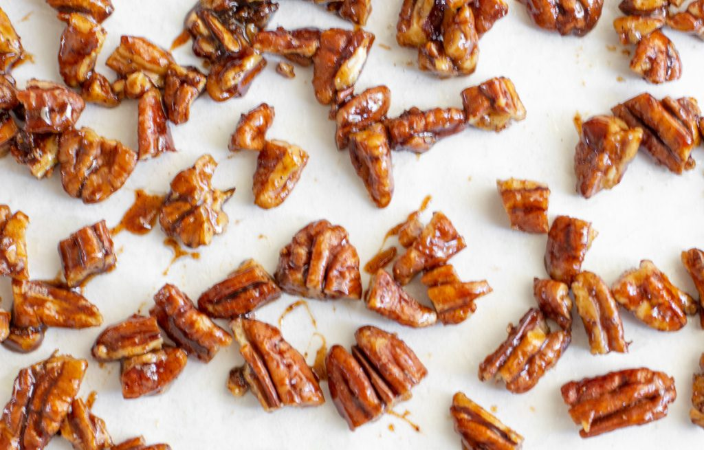 candied pecan pieces on white parchment paper
