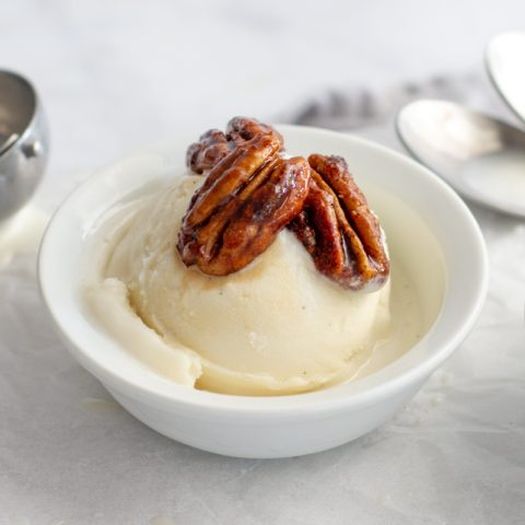 Candied pecans on top of scoop of vanilla ice cream in white bowl with ice cream sccop and spoons in background