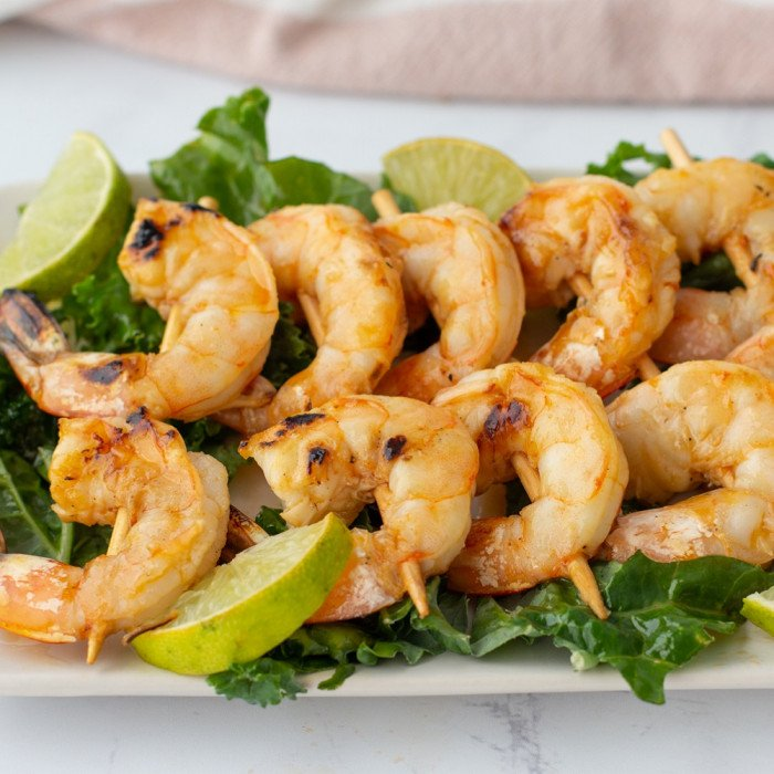 chili lime shrimp on plate with bed of lettuce and wedges of lime