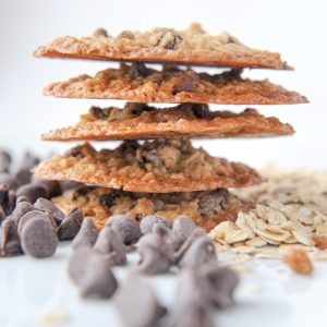close up of stack of gluten-free chocolate chip lace cookies with chocolate chips and oats scattered in front. White background.