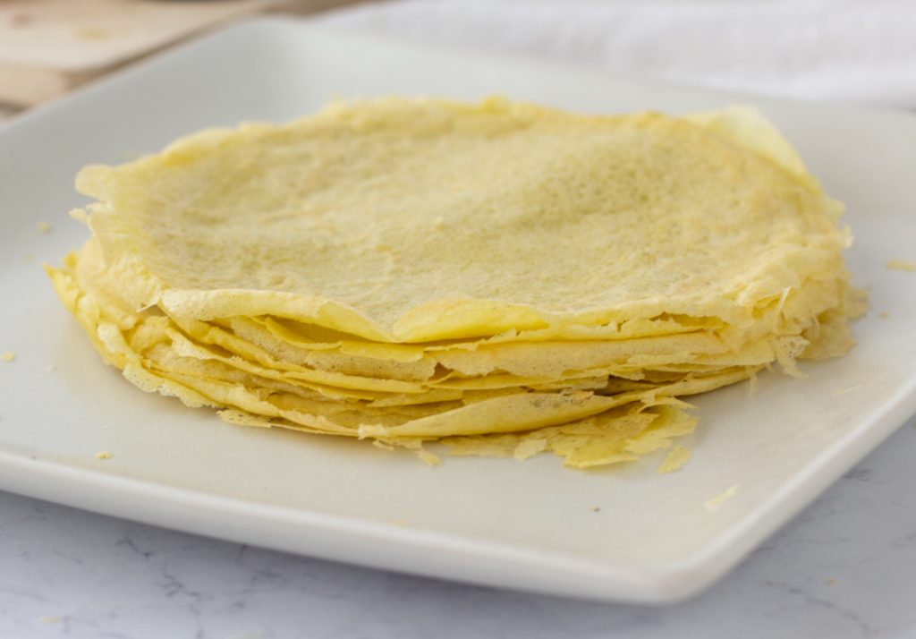 stack of gluten free crepe shells on square white plate