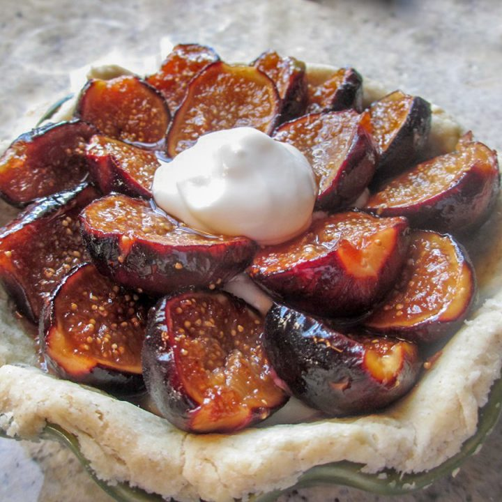 close up shot of gluten free fig pie topped with rings of glossy half figs and dollop of whipped cream in middle