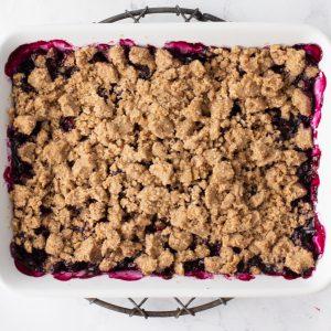 overhead shot of gluten-free blueberry crisp in white baking dish
