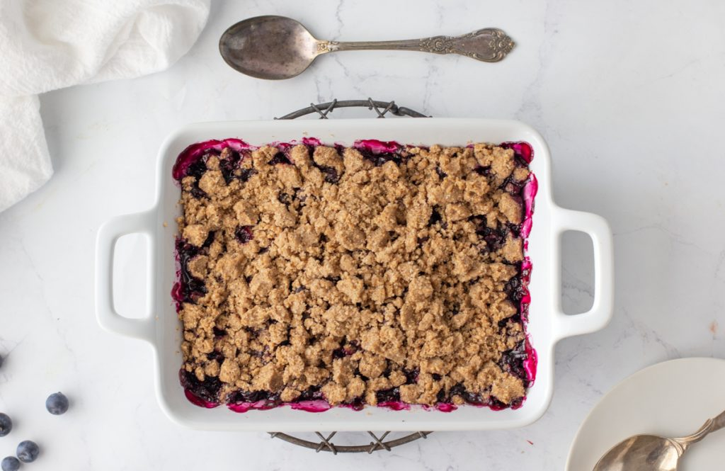 overhead shot of gluten free blueberry crisp in white baking dish with handles on a round wire rack and spoon above