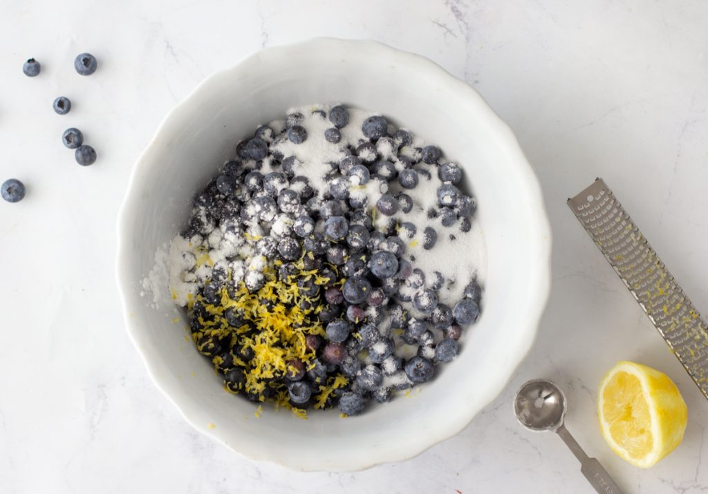 overhead view of white bowl with blueberries, lemon zest and corn starch. Measuring spoon, lemon half and zester on right. Scattered blueberries in upper left.