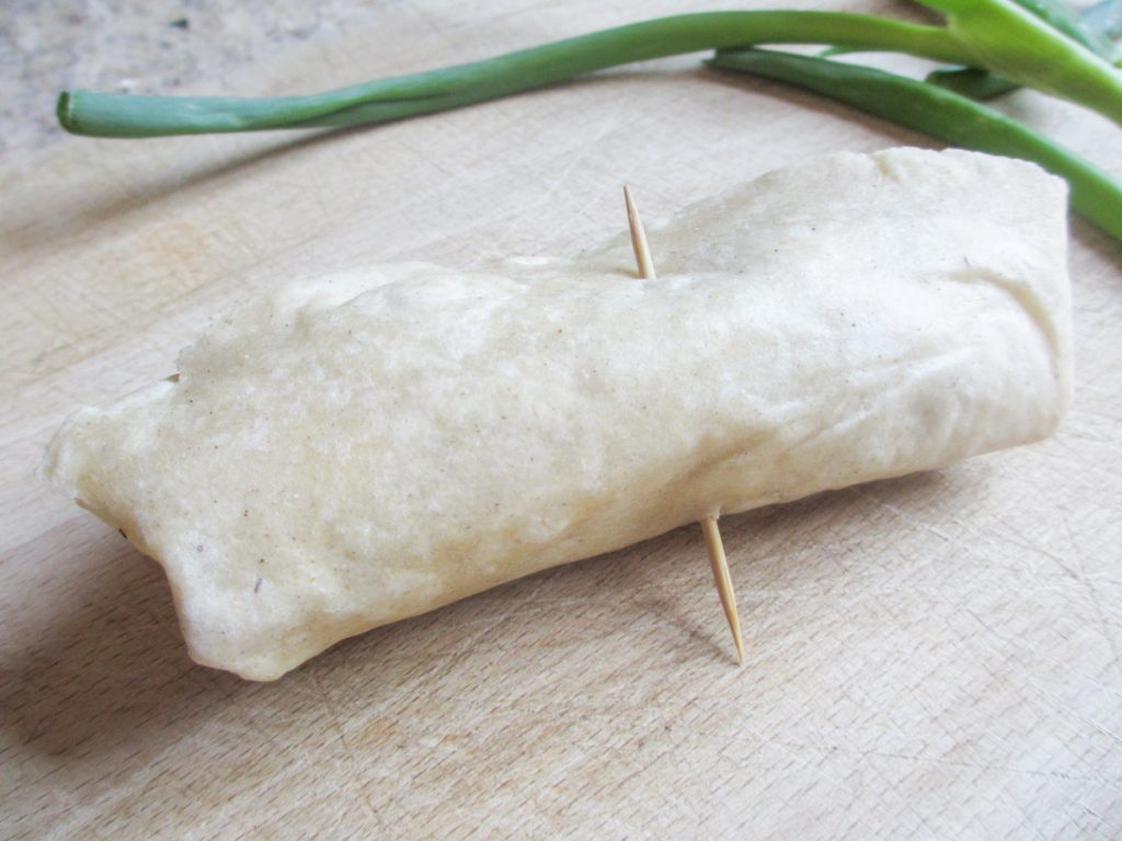 uncooked gluten-free egg roll with toothpick holding it closed
