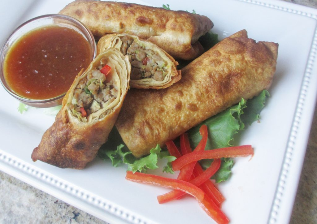 3 gluten free egg rolls on white plate with red bell pepper garnish and small glass bowl of peach dipping sauce