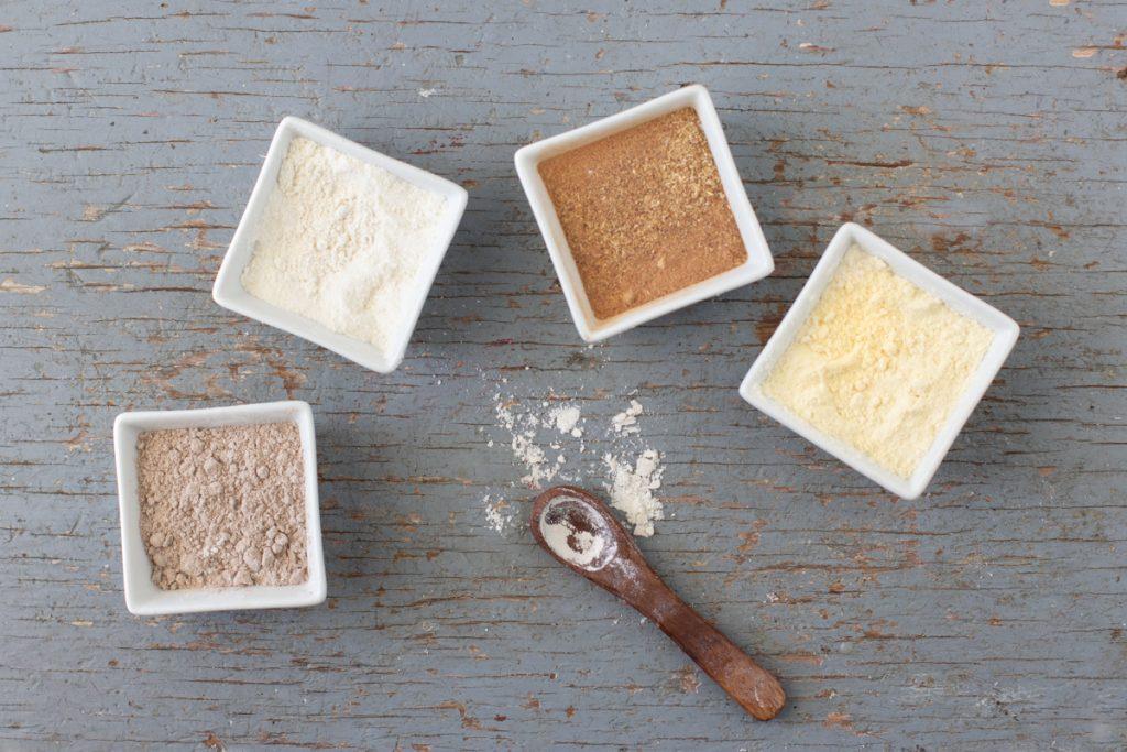 overhead view of square white bowls with teff flour, sorghum flour, mesquite flour, millet flour