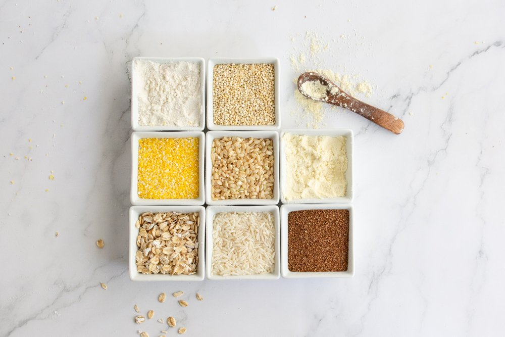 8 small square bowls arranged in grid with gluten-free grains, white rice, brown rice, corn meal, teff grain, oats, quinoa and sorghum flour on white marble background with small wood spoon