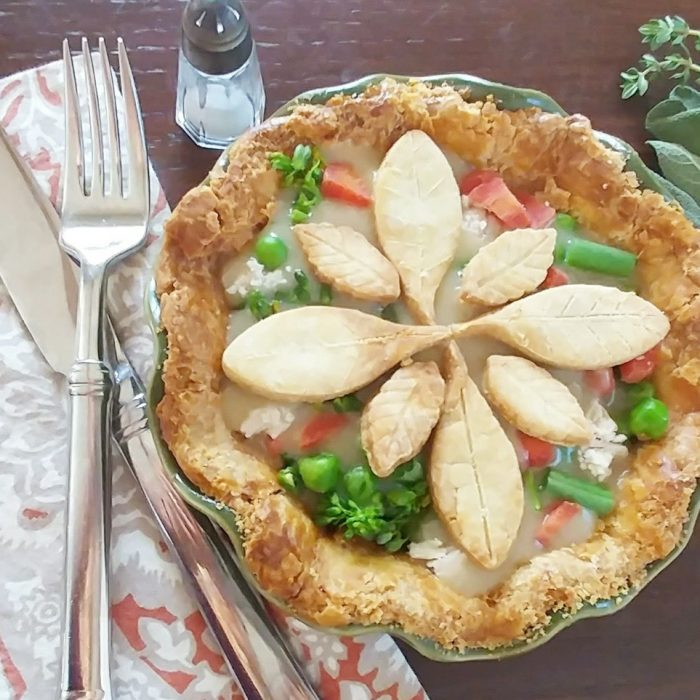gluten-free turkey pot pie leaf shaped crust pieces on top. fork and knife on orange and gray napkin on left, small salt shaker above and fresh sprigs of thyme and sage on right