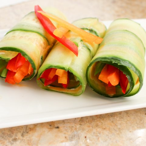 3 cucumber wrapped spring rolls on white plate with bell pepper garnish