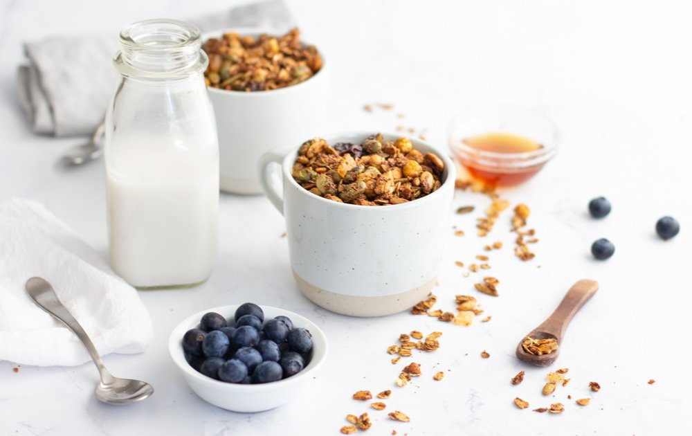 White mug with gluten free granola. Small white bowl with blueberries in front, small glass bowl with honey in right rear. Small wood spoon and scattered granola on right. Milk bottle and mug with granola in back left.