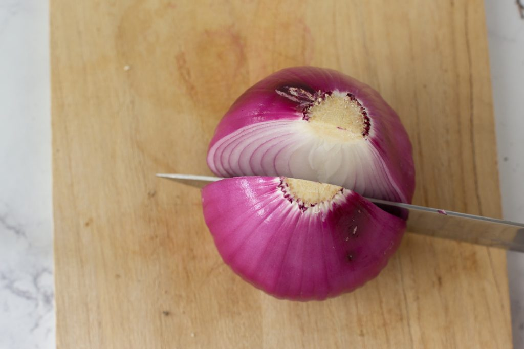 whole red onion on cutting board with knife cutting through root end