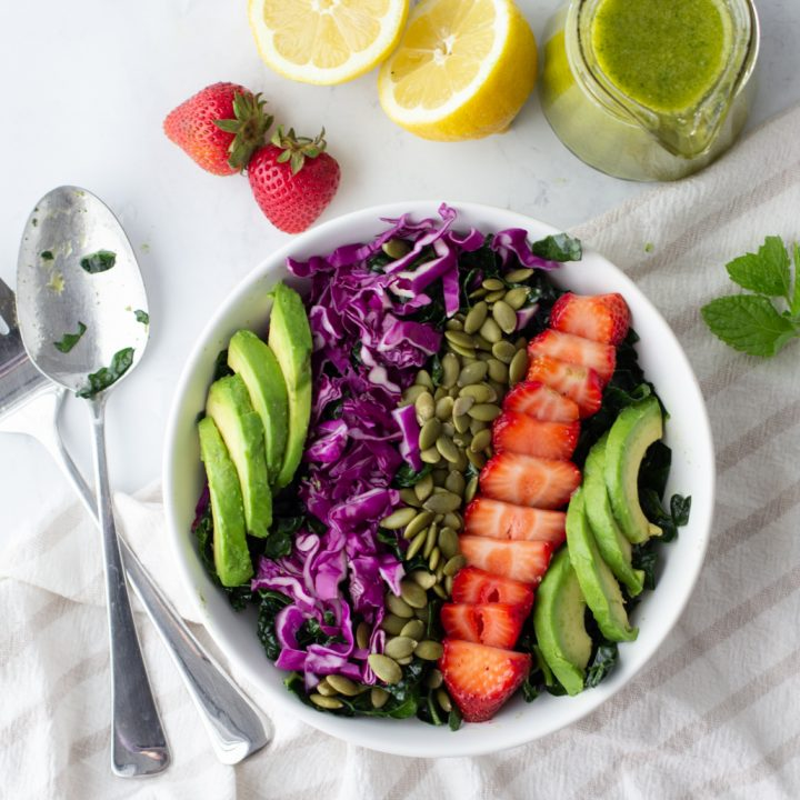 overhead view of white bowl with kale-strawberry salad topped with avocado slices, red cabbage, sliced strawberries. serving spoons on left, whole strawberries, cut lemon, jar of dressing above
