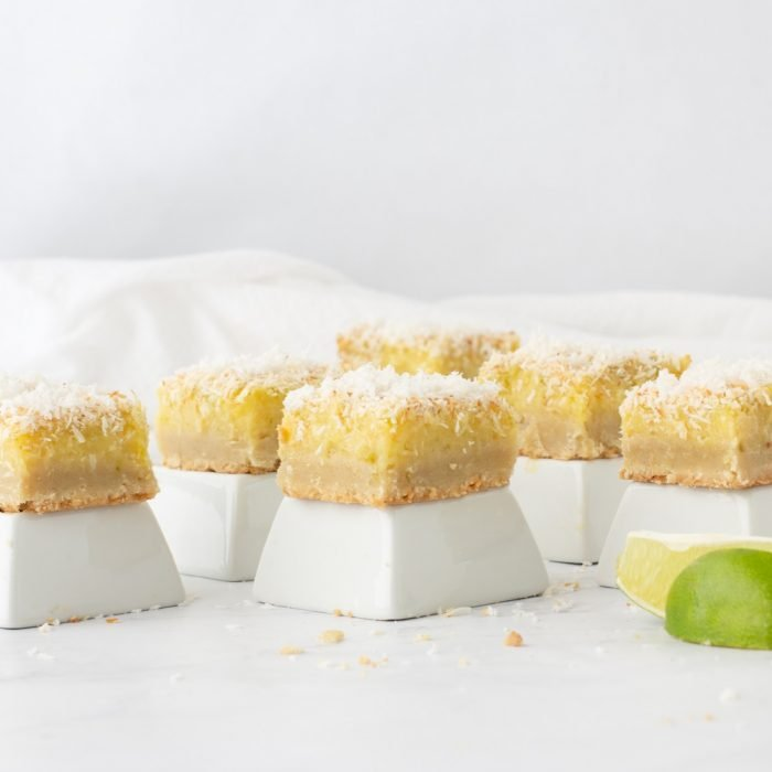 gluten-free lime coconut bars on square white pedestals with white marble background and lime wedges in forefront