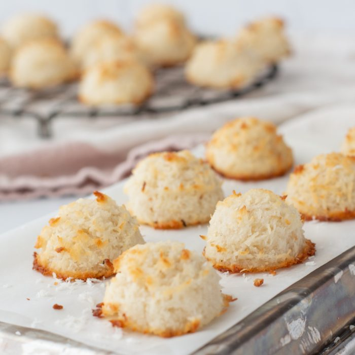 close up of gluten free coconut macaroons on white paper on top of upside down baking sheet