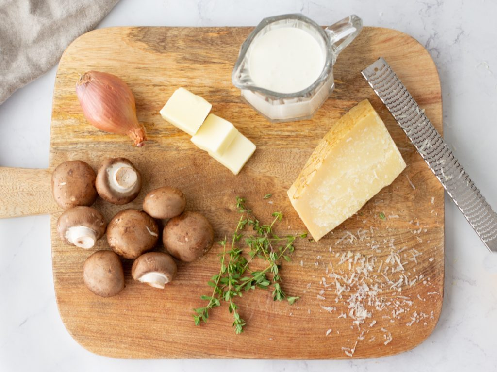 overhead of wood cutting board with crimini mushrooms, shallot bulb, cut stick of butter, small glass pitccher of cream, block of parmiggiano chees and sprigs of fresh thyme for filling in gluten-free crepes