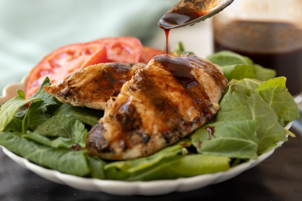Close up of white plate with Arugula salad, sliced tomato and grilled chicken breast. Spoon in upper right pouring raspberry balsamic glaze. Carafe with glaze in back.