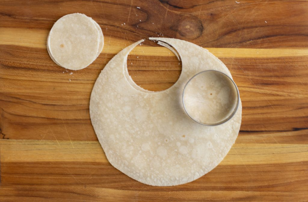 """gluten-free tortilla on wood board with 2 round pieces cut out sitting next to tortilla, 2 1/2"""" metal biscuit cutter on the tortilla"""