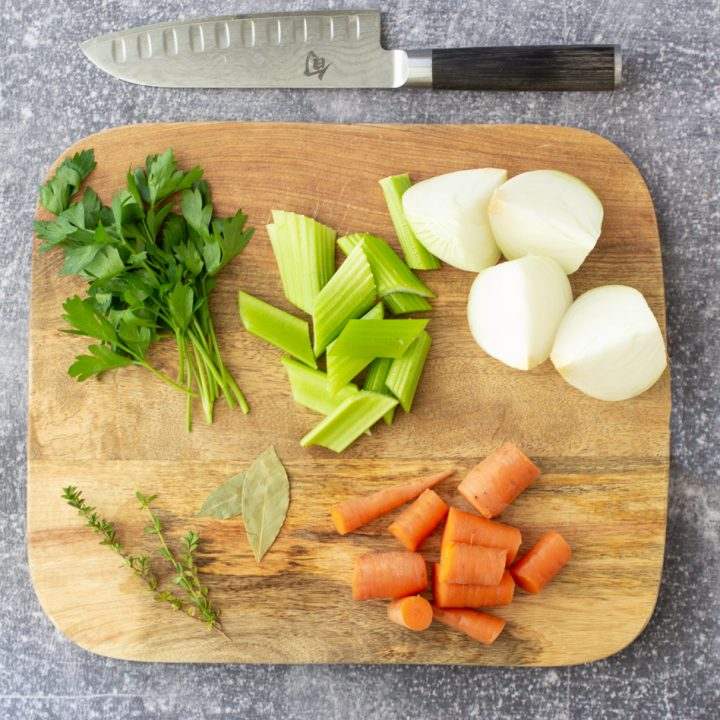 overhead shot of turkey stock ingredients - cut celery stalks, cut carrots, fresh parsley, quartered white onion, 2 bay leaves and sprigs of thyme on wood cutting board