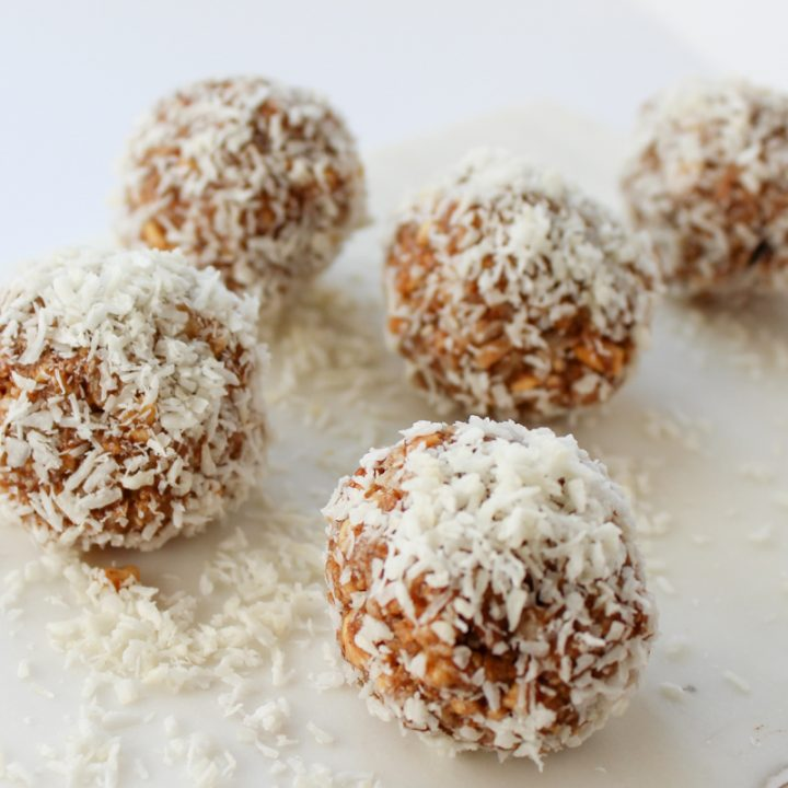 5 grain free energy bites in ball shape covered in shredded coconut on white background with chickpeas on right