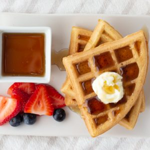 overhead shot of gluten free waffles with butter and syrup with blueberries and sliced strawberries on white plate