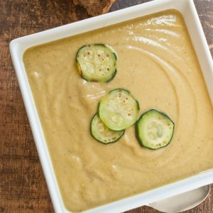 square white bowl of zucchini soup with cooked slice of zucchini garnish. Dark wood background with spoon on bottom and brown dinner roll on top