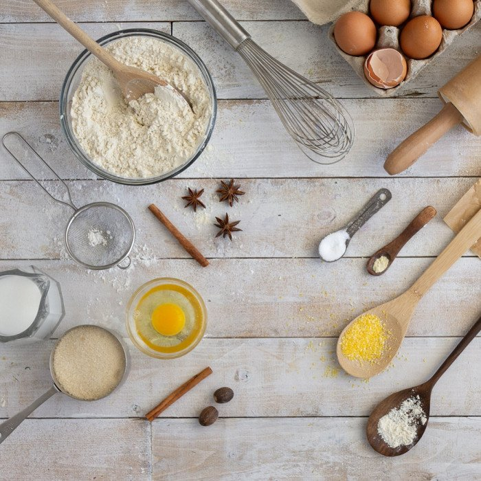 overhead view of baking tools and ingredients on white wood board