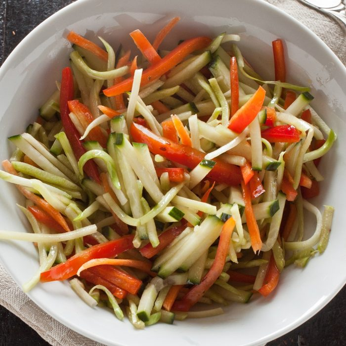 overhead shot of broccoli slaw with matchstick slices of cucumber and red bell pepper in white bowl on background of distressed painted black wood