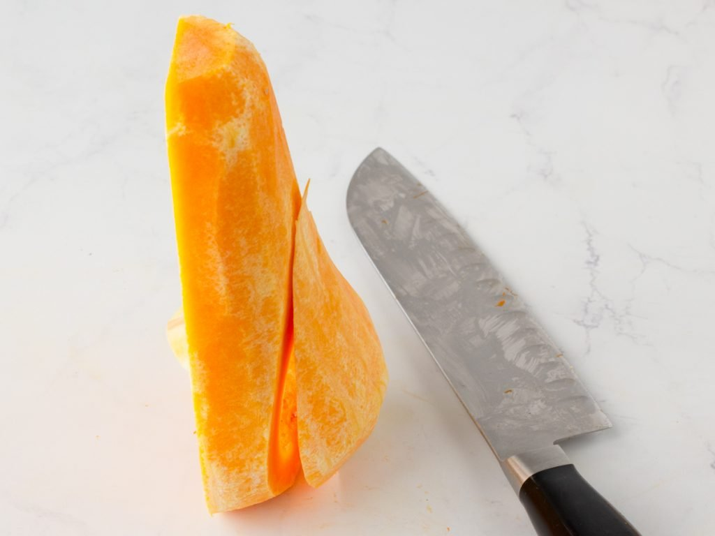Half of a raw butternut squash with vertical slice. Knife on left. White marble background.