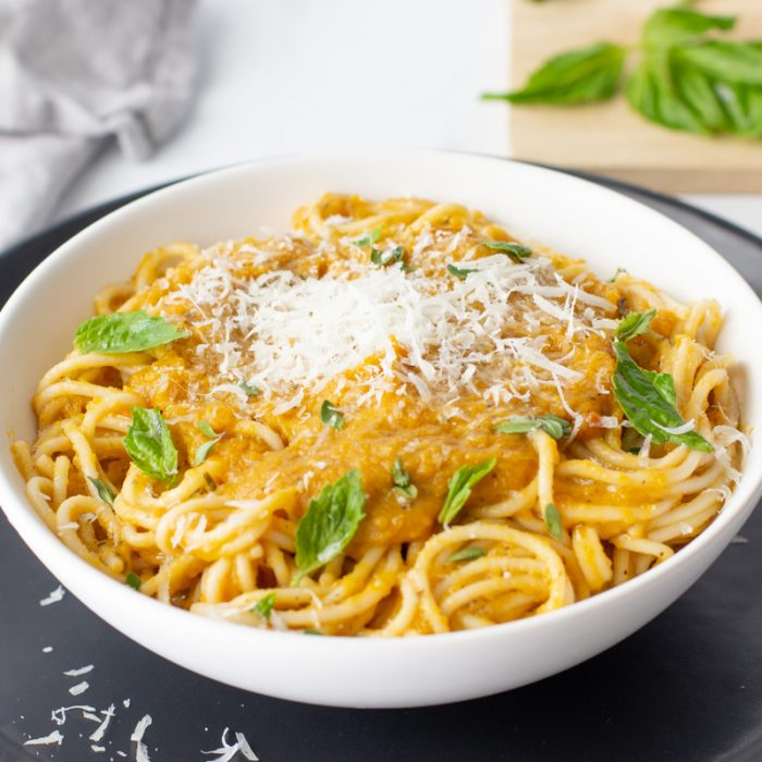 white bowl with spaghetti with low acid pasta sauce (butternut sqaush base) topped with grated Parmesan and basil leaves