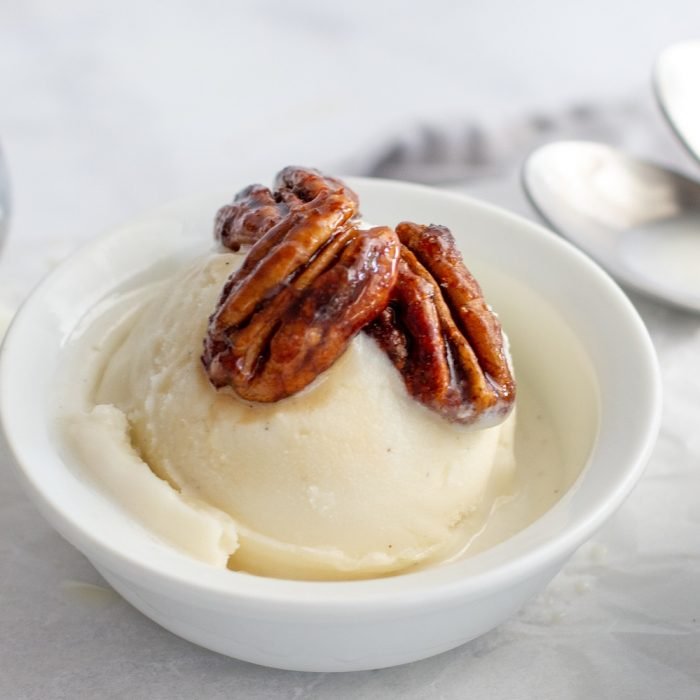 scoop of vanilla ice cream topped with spicy candied pecans in white bowl