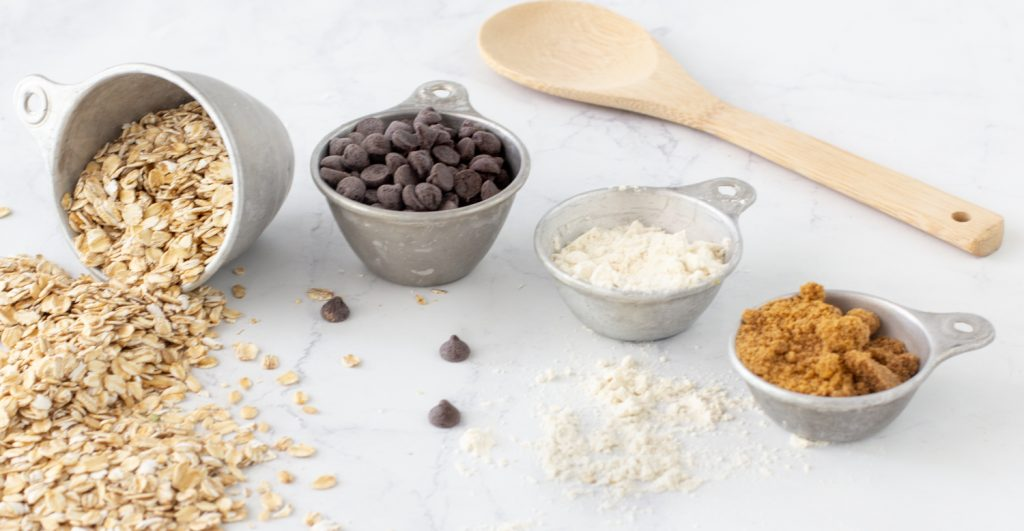 ingredients for gluten free cookies. rolled oats, chocolate chips, gluten-free flour and brown sugar in metal measuring cups on white background with wood spoon in back