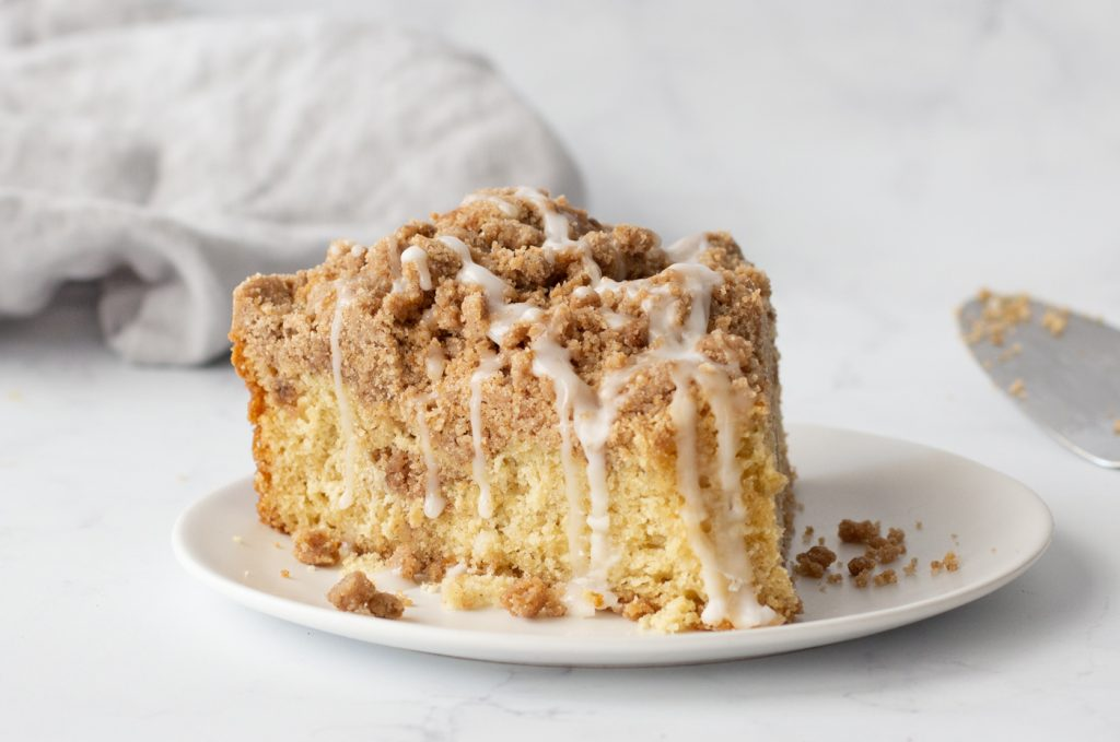 close up of large wedge of gluten-free cinnamon crumb cake with white icing dripping. Cake server partially visible on right. Gray napkin in background.