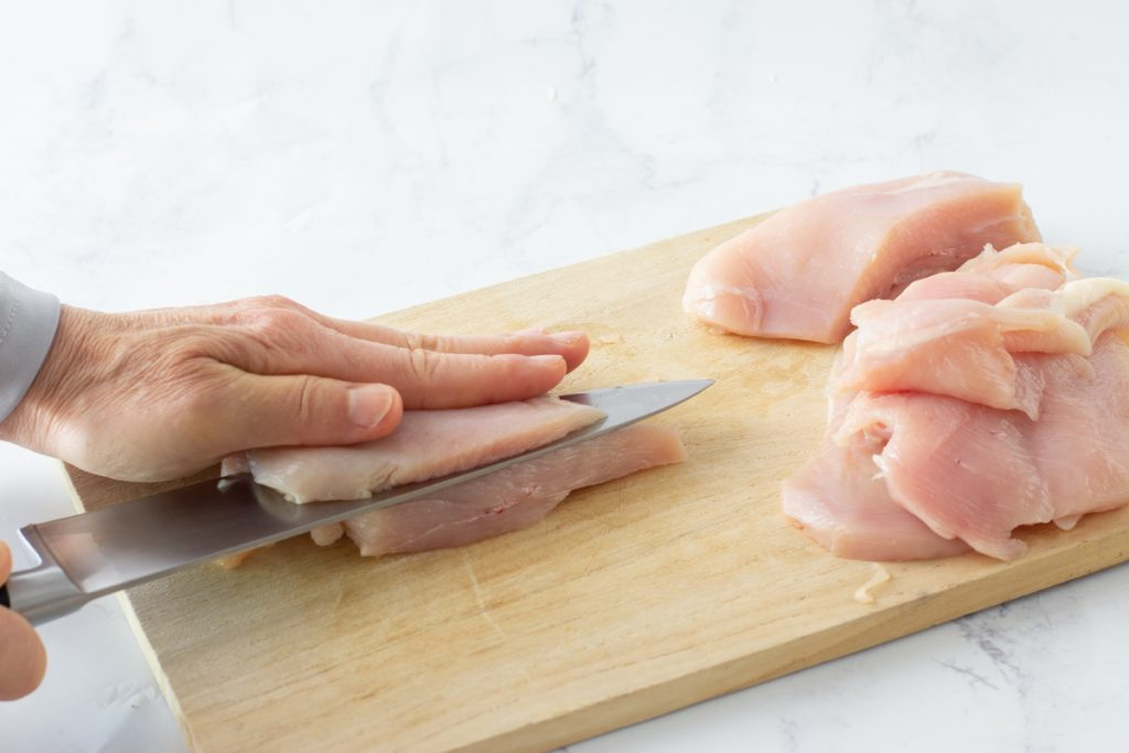 raw chicken breast on wood cutting board being cut in to thin pieces for gluten-free crispy coconut chicken