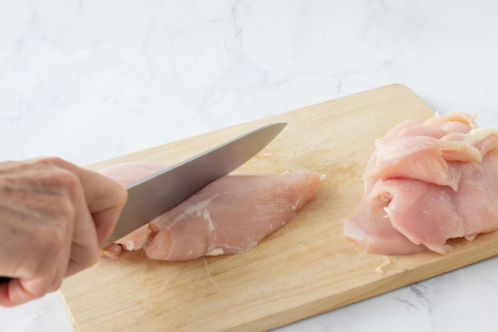 raw chicken breast on wood cutting board being cut in half