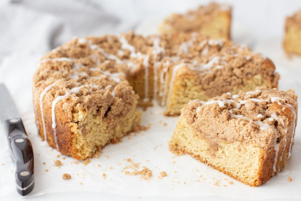 gluten-free cinnamon crumb cake topped with white icing. 1 piece cut out next to cake. 2 pieces on white plates in background. Knife on left. White background