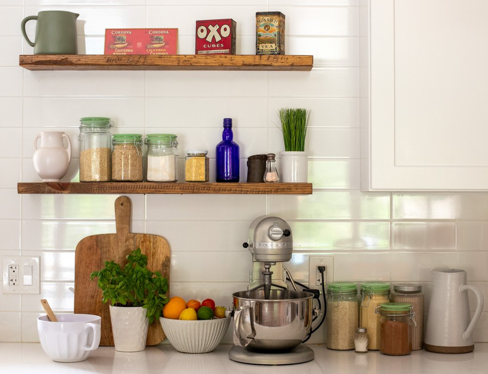white kitchen counter and backsplash. Wood Shelves with jars, bottles, vintage tins. Stand mixer bowl of fruit, cutting board and plant on counter.