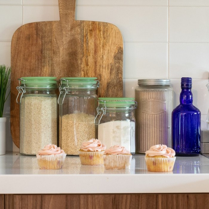 whit kitchen counter with jars of gluten free grains. Cutt board in back, cupcakes in front.