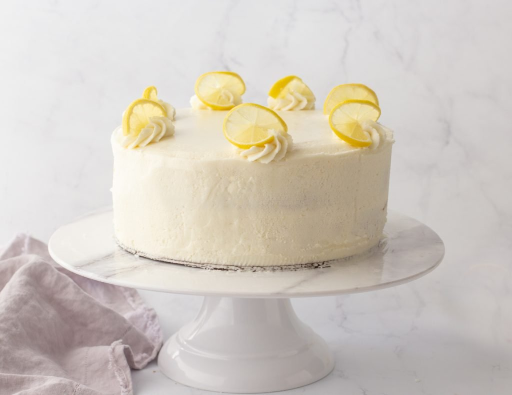 2 layer gluten-free lemon cake with buttercream frosting on white marble cake stand. slices of lemon on top of cake