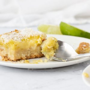 close up of gluten free lime coconut bar on white plate