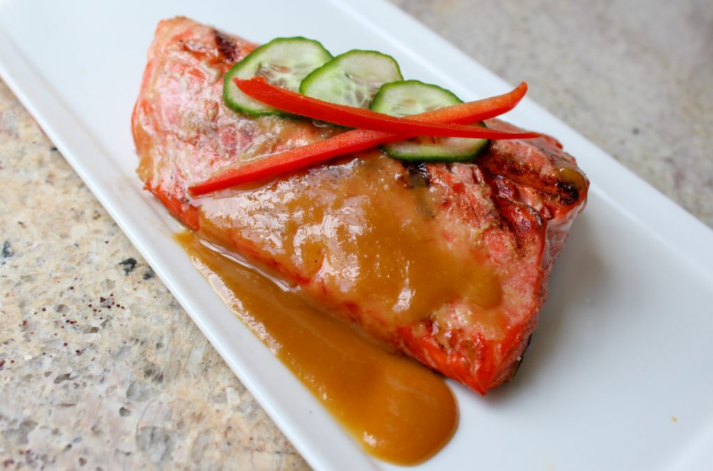 grilled salmon with miso-honey sauce on square white plate with cucumber and red pepper garnish