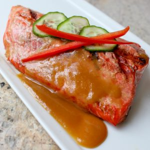 grilled salmon with miso sauce on square white plate with cucumber and red pepper garnish