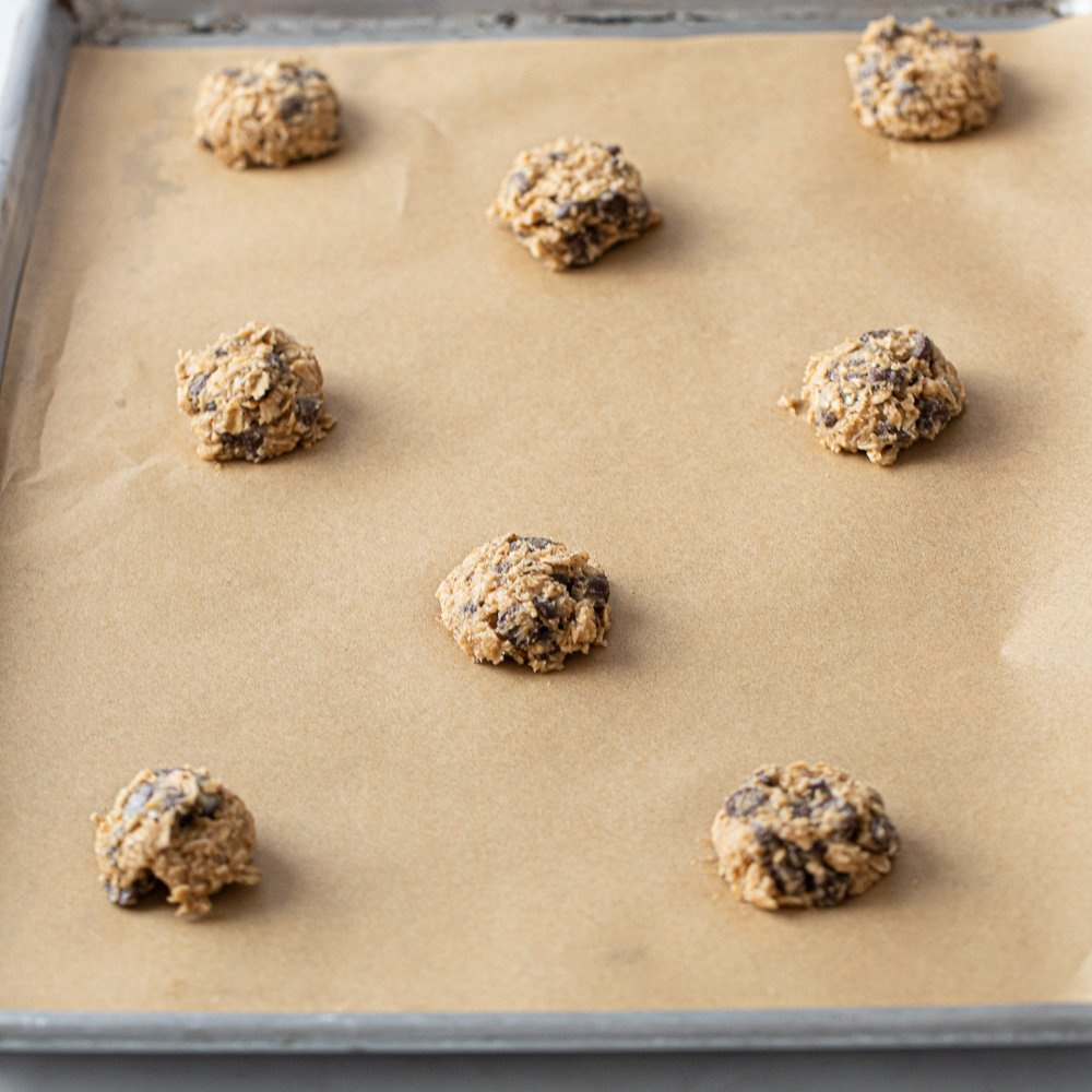 gluten free oat lace chip cookie dough portioned on parchment lined sheet pan.