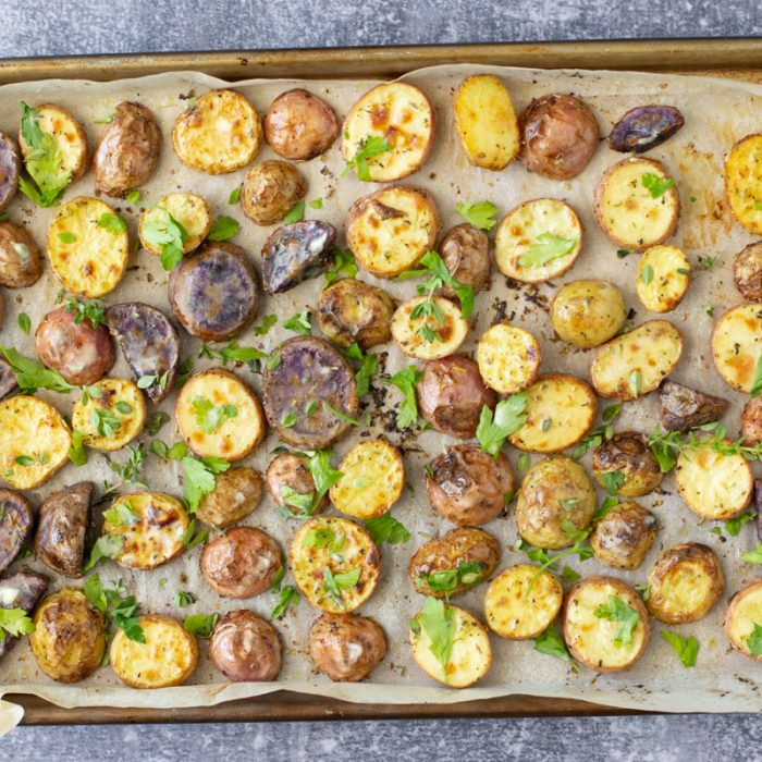 overhead view of sliced herb roasted potatoes on baking sheet
